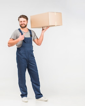 Bearded delivery man pointing finger at box