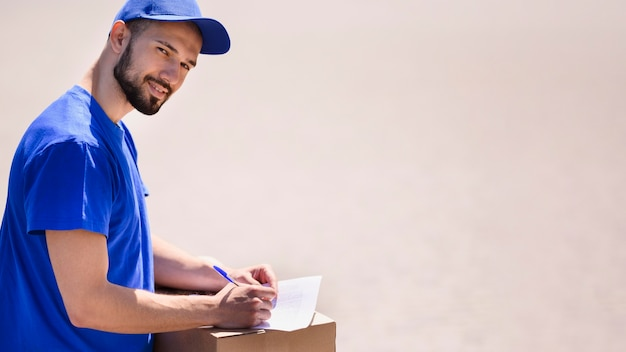 Uomo di consegna barbuto pronto a distribuire il pacco