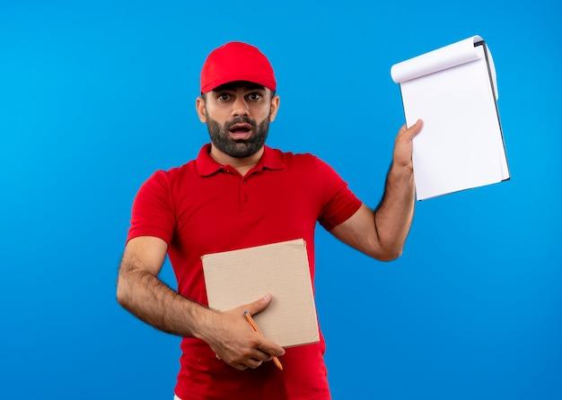 Uomo barbuto di consegna in uniforme rossa e cappuccio che tiene il pacchetto della scatola che mostra appunti che sembra sorpreso in piedi sopra la parete blu