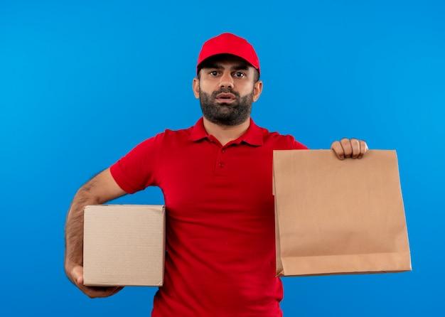 Uomo barbuto di consegna in uniforme rossa e cappuccio che tiene scatola e pacchetto di carta con la faccia seria che sta sopra la parete blu