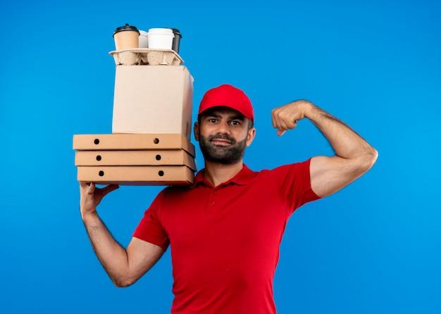 Uomo barbuto di consegna in uniforme rossa e cappuccio che tiene le scatole di cartone che osserva da parte con il sorriso sul viso alzando il pugno in piedi sopra la parete blu