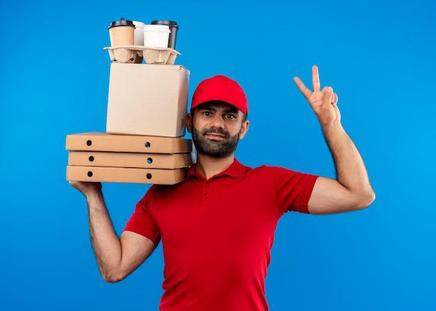 Uomo barbuto di consegna in uniforme rossa e cappuccio che tiene le scatole di cartone che guarda da parte con il sorriso sul viso che mostra il segno di vittoria in piedi sopra la parete blu