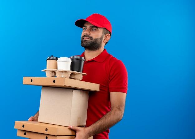 Uomo barbuto di consegna in uniforme rossa e cappuccio che tiene le scatole di cartone che osserva da parte con il sorriso sul viso in piedi sopra la parete blu