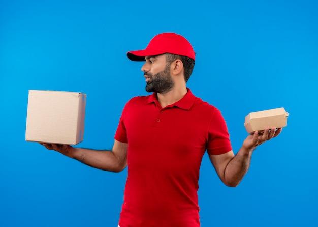 Uomo barbuto di consegna in uniforme rossa e cappuccio che tiene le scatole di cartone che sembrano confusi avendo dubbi in piedi sul muro blu