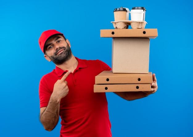 Uomo barbuto di consegna in uniforme rossa e cappuccio che tiene le scatole di cartone puntando con il dito verso di loro con il sorriso sul viso in piedi sopra la parete blu