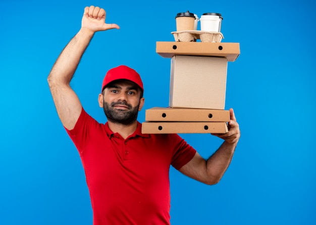 Bearded delivery man in red uniform and cap holding cardboard boxes  with smile on face showing thumbs up standing over blue wall