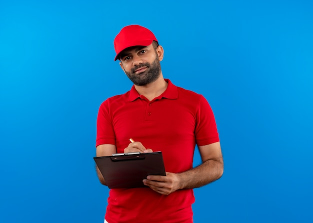 Bearded delivery man in red uniform and cap holding clipboard writing looking confident standing over blue wall