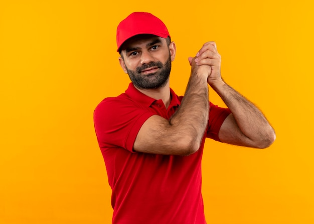 Bearded delivery man in red uniform and cap holding hands together making team work gesture feeling thankful standing over orange wall