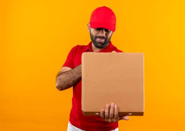 Uomo barbuto di consegna in uniforme rossa e cappuccio che tiene la scatola della pizza aperta guardandolo con una faccia buffa in piedi sopra la parete arancione