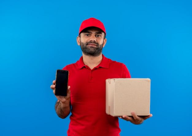 Uomo barbuto di consegna in uniforme rossa e cappuccio che tiene aperto la scatola della pizza che mostra smartphone con espressione sicura in piedi sopra la parete blu