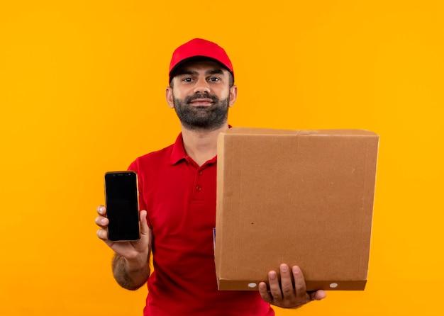 Uomo barbuto di consegna in uniforme rossa e cappuccio che tiene aperto la scatola della pizza che mostra smartphone con espressione sicura in piedi sopra la parete arancione