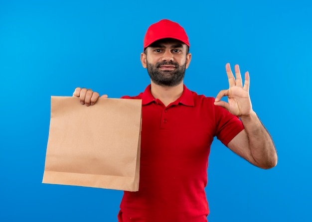 Bearded delivery man in red uniform and cap holding paper package smiling showing ok sign standing over blue wall