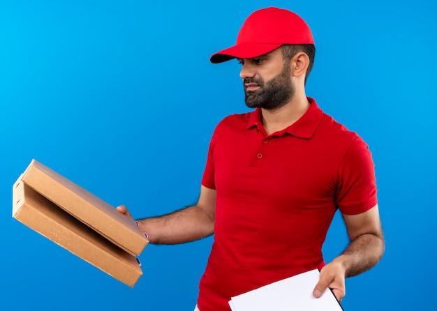 Uomo barbuto di consegna in uniforme rossa e cappuccio che tiene scatole per pizza e appunti con pagine vuote che sembrano confuse avendo dubbi in piedi sul muro blu
