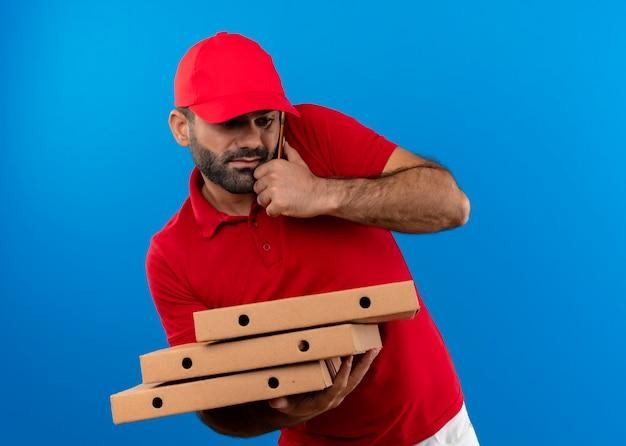 Uomo barbuto di consegna in uniforme rossa e cappuccio che tiene pila di scatole per pizza che sembra confuso mentre parla al telefono cellulare in piedi sopra la parete blu