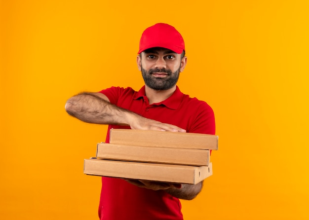 Bearded delivery man in red uniform and cap holding stack of pizza boxes offering with friendly smile standing over orange wall