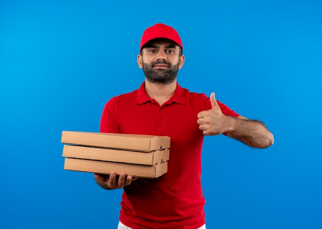 Bearded delivery man in red uniform and cap holding stack of pizza boxes showing thumbs up smiling confident standing over blue wall