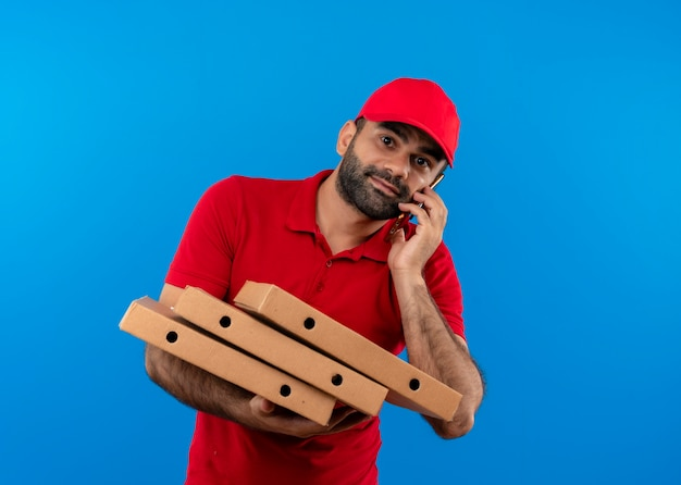 Uomo barbuto di consegna in uniforme rossa e cappuccio che tiene pila di scatole per pizza sorridente mentre parla al telefono cellulare in piedi sopra la parete blu