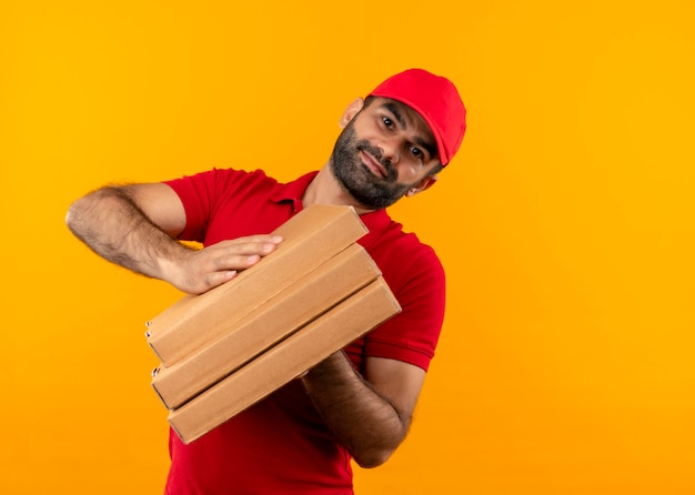 Bearded delivery man in red uniform and cap holding stack of pizza boxes  with smile on face standing over orange wall