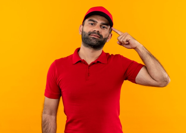 Bearded delivery man in red uniform and cap pointing with finger his temple focused on task standing over orange wall