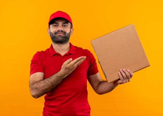 Uomo barbuto di consegna in uniforme rossa e cappuccio che presenta la scatola della pizza con il braccio della sua mano che sorride fiducioso in piedi sopra la parete arancione