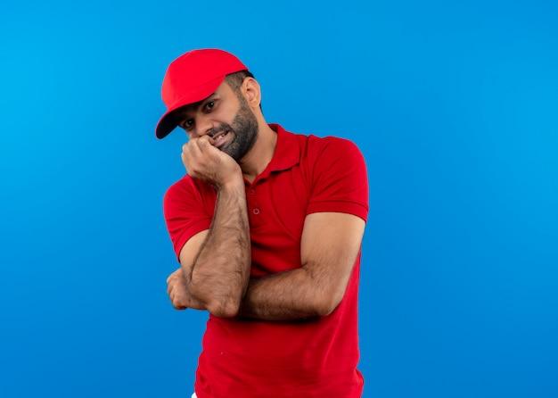 Uomo barbuto di consegna in uniforme rossa e berretto unghie mordaci nervose e stressate in piedi sopra la parete blu