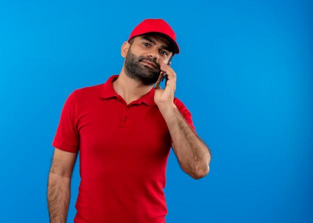 Uomo barbuto di consegna in uniforme rossa e cappuccio parlando al telefono cellulare cercando fiducioso in piedi oltre la parete blu
