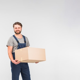 Bearded delivery man standing with big box