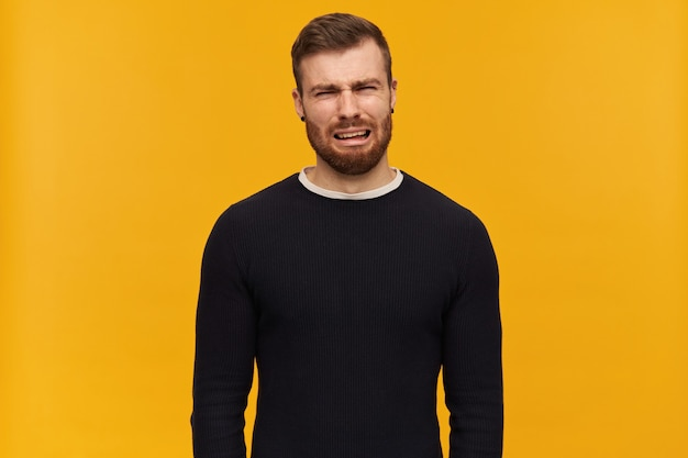 Bearded depressed guy, unhappy looking man with brunette hair. has piercing. wearing black sweater. crying and wry face full of tears.  isolated over yellow wall