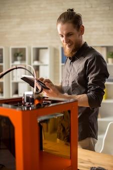 Bearded designer using 3d printer