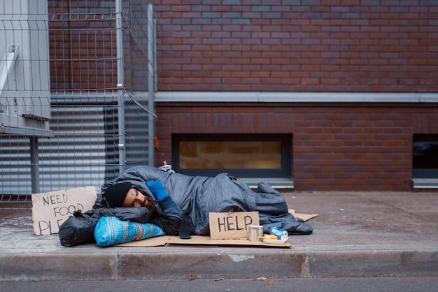 ヘルプサインでひげを生やした汚いホームレスは街の通りにあります。