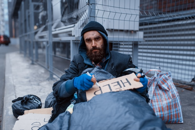 Bearded dirty homeless writes help sign on city street.
