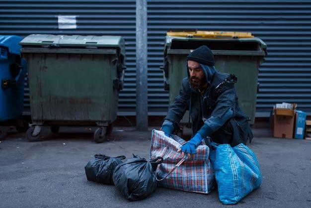 街の通りのゴミ箱でひげを生やした汚い貧しい人々。