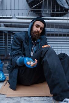 街の通りで物乞いをしているひげを生やした汚い貧しい人々。