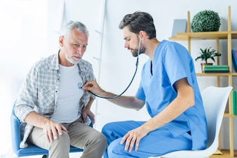 Bearded doctor examining lungs of patient