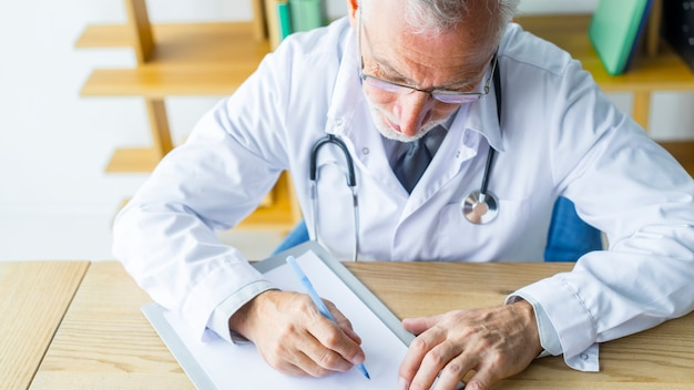 Bearded doctor making notes