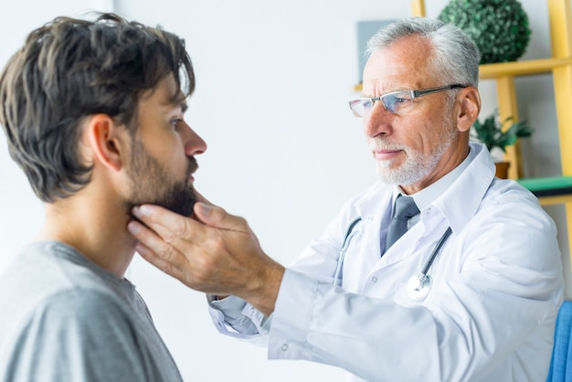 Bearded doctor rubbing lymph nodes of patient