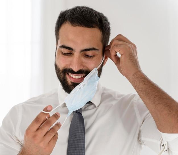 Бородатый врач снимает медицинскую маску