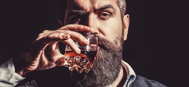 ひげを生やした飲み物のコニャック。ソムリエは飲み物を味わいます。ウイスキーのグラスを持っている男。ウイスキーをすすりながら。厚いひげを持つ男の肖像画。マッチョな飲酒。デグステーション、テイスティング