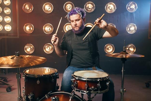 Бородатый барабанщик с яркими волосами на сцене с огнями в винтажном стиле. музыкальный исполнитель, живая музыка
