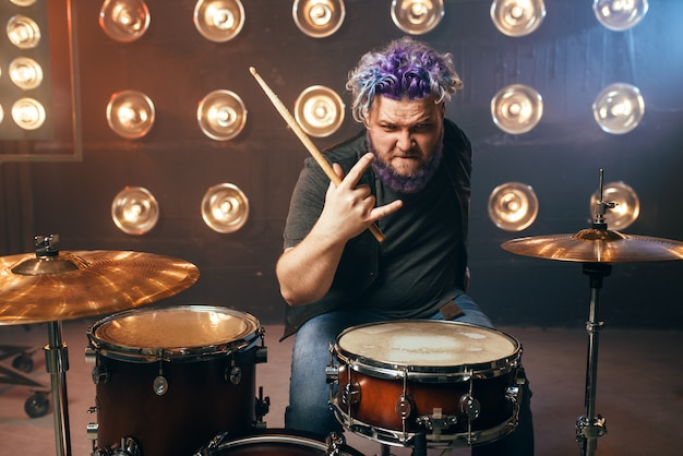 Bearded drummer with colorful hair, rock performer on the stage with lights