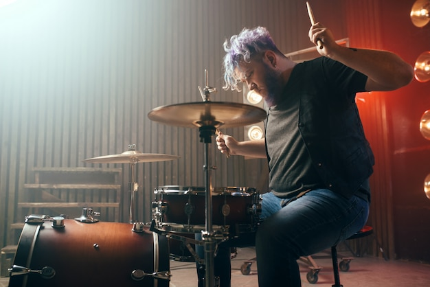 Bearded drummer with colorful hair on the stage