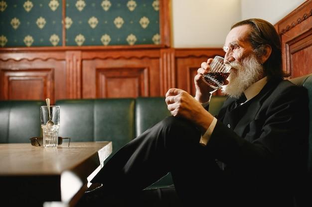 Бородатый пожилой бизнесмен. мужчина пьет виски. старший в черном костюме.