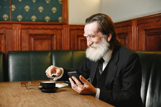 Бородатый пожилой бизнесмен. мужчина с кофе. старший в черном костюме.