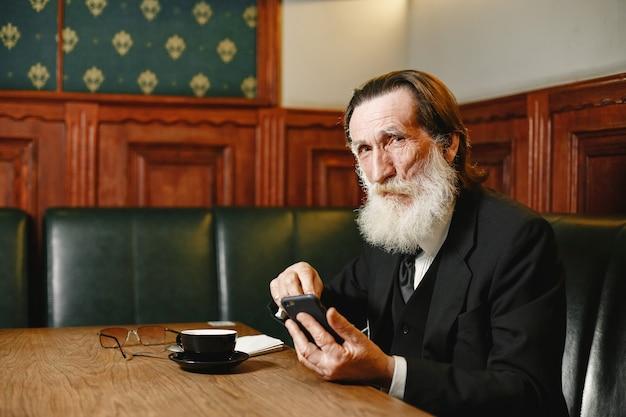 あごひげを生やした年配のビジネスマン。コーヒーを持つ男。黒のスーツを着た先輩。