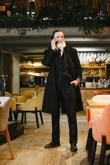 수염 된 노인 사업가입니다. 휴대 전화를 가진 남자입니다. 검은 양복에 수석.