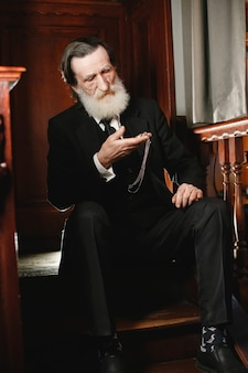 수염 된 노인 사업가입니다. 오래 된 시계를 가진 남자입니다. 검은 양복에 수석.