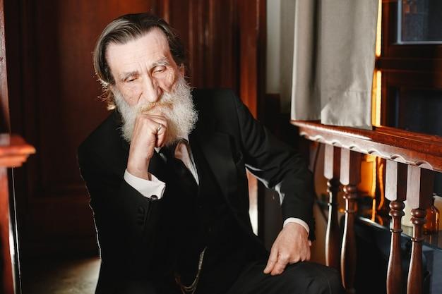 Бородатый пожилой бизнесмен. человек со старыми часами. старший в черном костюме.
