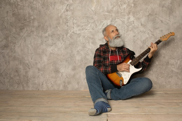 Бородатый пожилой мужчина играет на гитаре