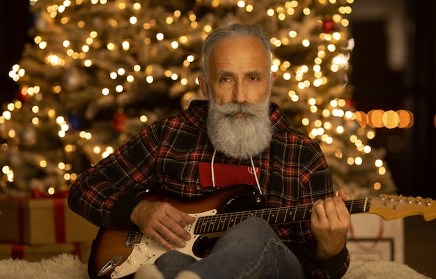 Bearded elderly man is playing guitar