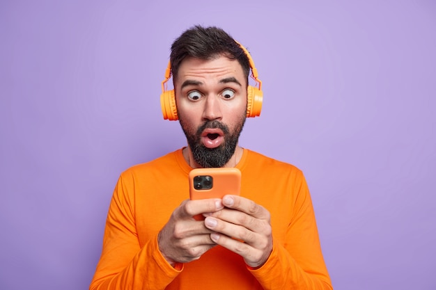 Bearded emotive man stares at smartphone display uses mobile phone app holds smartphone stares impressed, uses wireless headphones for listening music